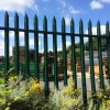 A green Lochrin Classic fence installed around a fencing supplies yard.