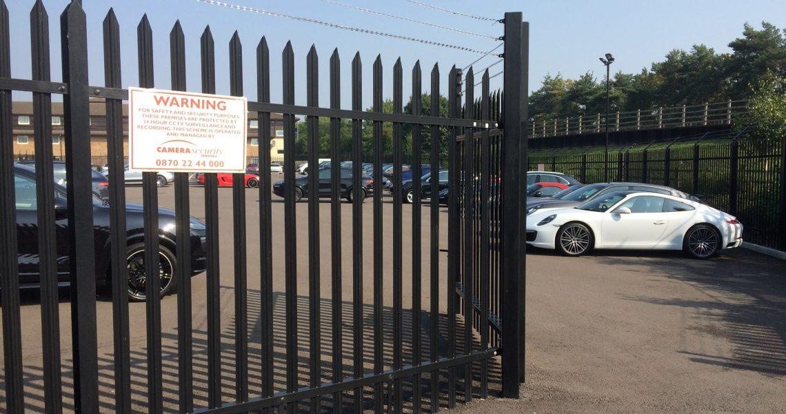 A black Lochrin Classic fence installed around a car dealership.